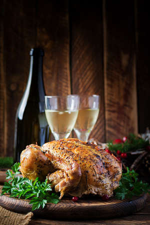 Baked turkey or chicken. The Christmas table is served with a turkey, decorated with bright tinsel. Fried chicken, table setting. Christmas dinner. Standard-Bild