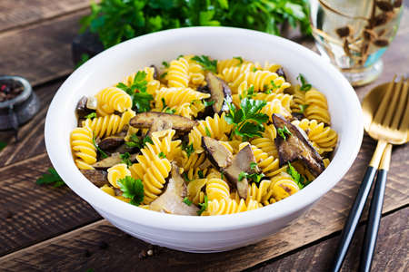 Fusilli pasta gluten free with forest mushrooms on a white plate. Vegetarian / vegan food. Italian cuisine.