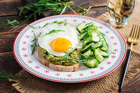 Healthy breakfast. Christmas brunch. Avocado sandwich with fried egg and cucumber with arugula on wooden table. Standard-Bild