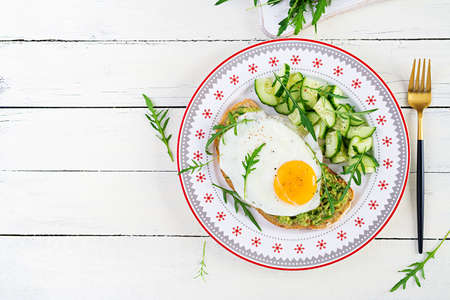 Healthy breakfast. Christmas brunch. Avocado sandwich with fried egg and fresh salad cucumber with arugula for healthy breakfast or snack. Top view, copy space Standard-Bild
