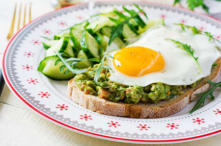 Healthy breakfast. Christmas brunch. Avocado sandwich with fried egg and fresh salad cucumber with arugula for healthy breakfast or snack. Standard-Bild