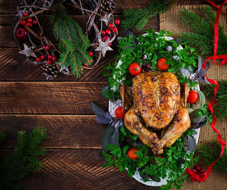 Baked turkey or chicken. The Christmas table is served with a turkey, decorated with bright tinsel. Fried chicken, table setting. Christmas dinner. Top view, overhead, copy space Standard-Bild