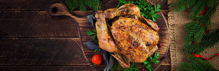Baked turkey or chicken. The Christmas table is served with a turkey, decorated with bright tinsel. Fried chicken, table setting. Christmas dinner. Top view, banner, copy space Standard-Bild