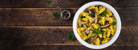 Fusilli pasta gluten free with forest mushrooms on a white plate. Vegetarian / vegan food. Italian cuisine. Top view, flat lay, copy space