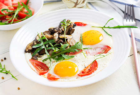 Tasty breakfast - fried eggs, forest mushrooms, tomatoes and arugula. Lunch food. Standard-Bild