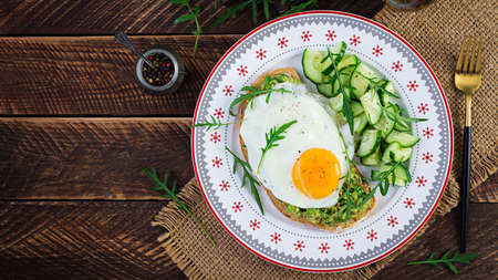 Healthy breakfast. Christmas brunch. Avocado sandwich with fried egg and cucumber with arugula on wooden table. Top view, copy space