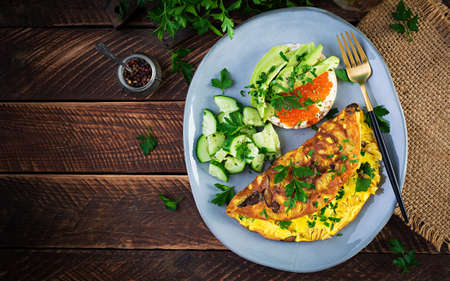 Omelette with forest mushroom, fusilli pasta and sandwich wich red caviar, avocado on plate. Frittata - italian omelet. Top view, overhead, copy space