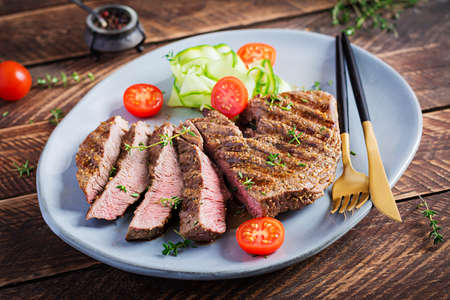 Grilled juicy steak medium rare beef with spices and fresh salad.