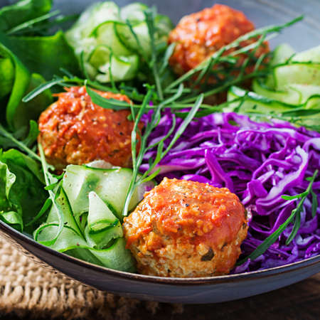 Keto / ketogenic food. Chicken meatballs and salad on wooden background. Dinner. Buddha bowl. Standard-Bild