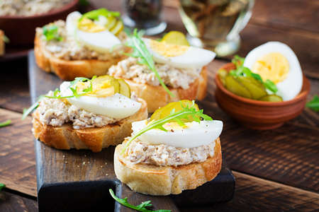 Toasted bread with a salted codfish mousse on wooden cutting board. Mackerel paste on toasts from fried bread. Scandinavian cuisine