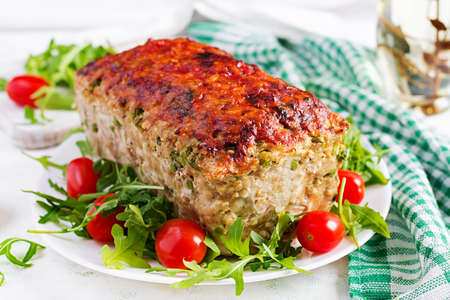 Tasty homemade ground baked chicken meatloaf with green peas and sliced broccoli on white table. Food american meat loaf