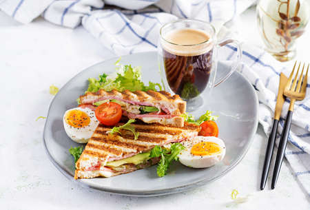 Grilled club sandwich panini with ham, tomato, cheese, avocado and cup of coffee. Delicious breakfast or snack.