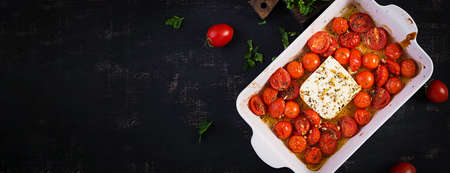 Fetapasta. Trending viral Feta bake pasta recipe made of cherry tomatoes, feta cheese, garlic and herbs in a casserole dish. Top view, banner, copy space.