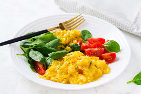 Breakfast. Scrambled eggs with cherry tomatoes, spinach and corn. Imagens
