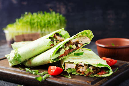 Fresh tortilla wraps with chicken and fresh vegetables on wooden board. Chicken burrito. Healthy food concept. Mexican cuisine.