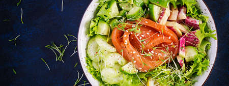 Ketogenic diet breakfast. Salt salmon salad with greens, cucumbers, celery and watermelon radish. Keto, paleo lunch. Top view, above