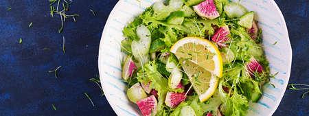 Salad from watermelon radish, cucumber, celery and lettuce leaves. Vegan food. Dietary menu. Top view, overhead, copy space