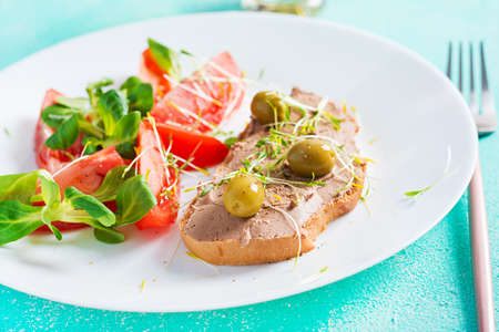 Fresh homemade chicken liver pate on bread and tomatoes salad. Breakfast.