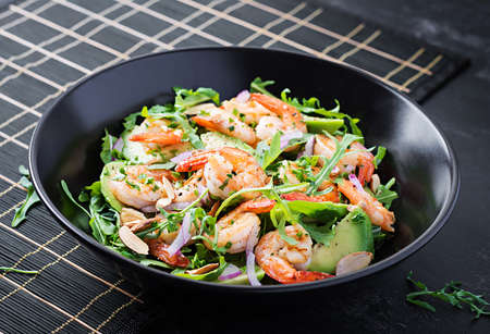 Salad of prawns. Salad of shrimps, arugula, avocado slice, red onion and almond nuts. Healthy concept.