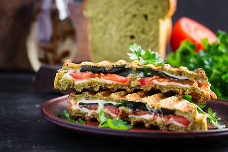 Vegetarian sandwich panini with spinach leaves, tomatoes and cheese on a dark table. Toast with cheese. 免版税图像