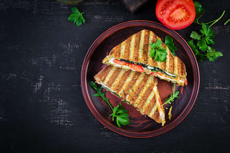 Vegetarian sandwich panini with spinach leaves, tomatoes and cheese on a dark table. Toast with cheese. Top view, overhead, copy space 免版税图像