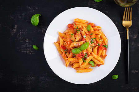 Classic italian pasta penne alla arrabiata with basil and freshly grated parmesan cheese on dark table. Penne pasta with chili sauce arrabbiata. Top view, above, copy space