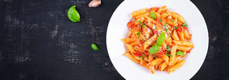 Classic italian pasta penne alla arrabiata with basil and freshly grated parmesan cheese on dark table. Penne pasta with chili sauce arrabbiata. Top view, above, banner