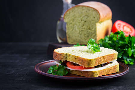 Spinach bread and a sandwich with cheese, tomatoes and herbs. Healthy lunch.
