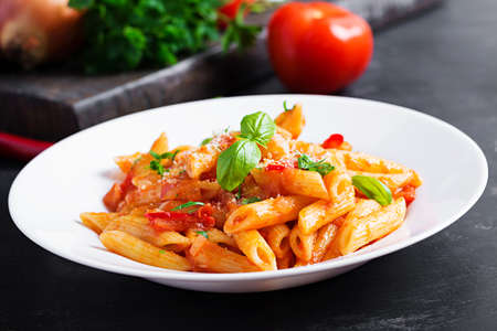 Classic italian pasta penne alla arrabiata with basil and freshly grated parmesan cheese on dark table. Penne pasta with chili sauce arrabbiata.