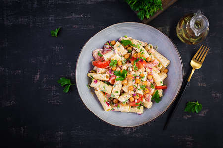 Vegetarian vegetable pasta. Pasta rigatoni with tomato, red onion, parsley and fried chickpeas with nut sauce. Vegan food. Top view, overhead 免版税图像