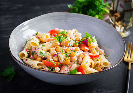 Vegetarian vegetable pasta. Pasta rigatoni with tomato, red onion, parsley and fried chickpeas with nut sauce. Vegan food.