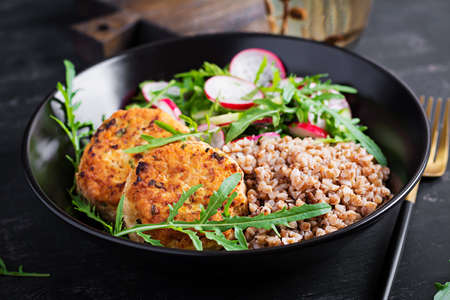 Healthy dinner. Lunch bowl with buckwheat porridge, fried chicken cutlets and fresh vegetable salad of arugula, cucumber and radish.