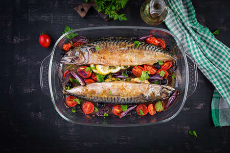 Baked mackerel with herbs and lemon and vegetables. Healthy dinner. Top view, flat lay 免版税图像