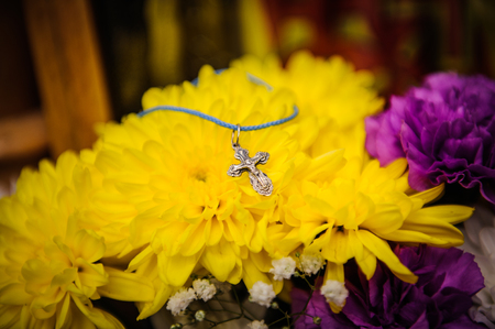 the believer: Orthodox cross lies on a background of flowers Stock Photo