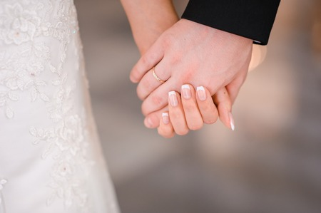 Bride and groom holding hands outdoors Stock Photo