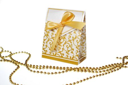 fancy box: white box with festive ornaments and golden ribbon and beads Stock Photo