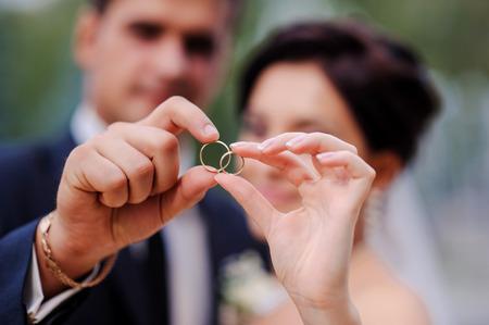 anillos de matrimonio: novia y el novio de la mano en un anillo