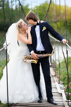 Bride and groom on the bridge with a saxophone photo