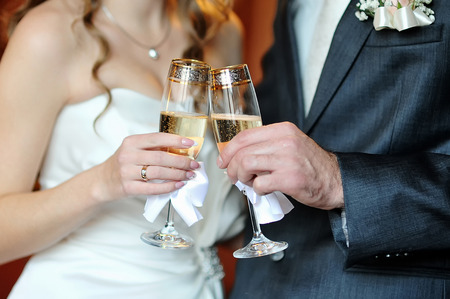 closeup hands of the bride and groom with glasses of champagne Foto de archivo