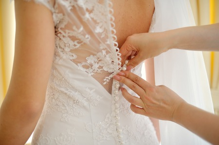 beautiful dress: Bridesmaid is helping the bride to dress.