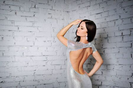 poses: Beautiful luxury woman model posing in dress with open back. Fashion evening make-up, dark lips, long straight hair, slim voluptuous body shapes.