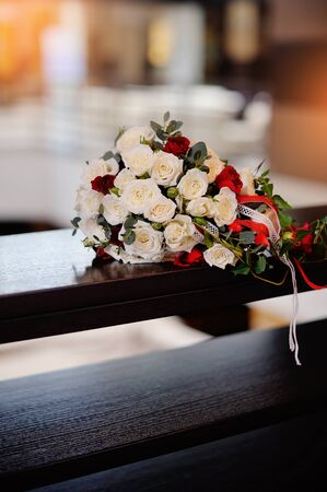 bridal bouquet of roses on a wood table. photo