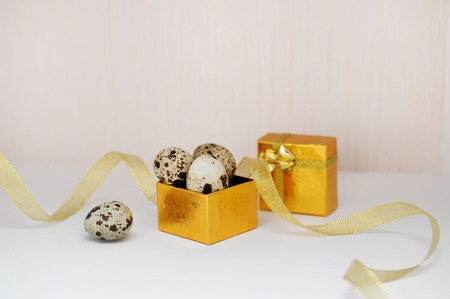 eastertime: golden box with Easter eggs and ribbon.