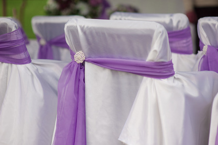 wedding chairs: beautiful white wedding chairs decorated with purple bows. Stock Photo