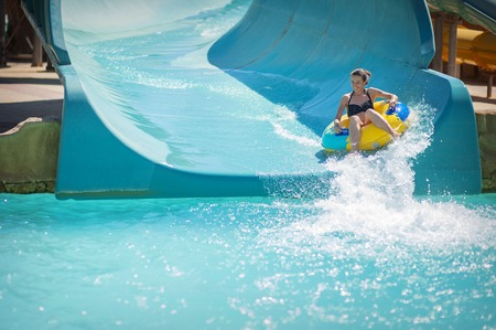 beautiful girl pulls off the slides at the water park. Stockfoto