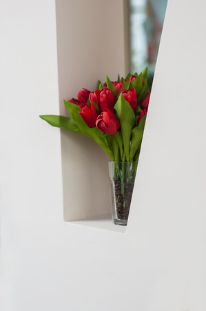 bouquet of red tulips on the windowsill photo