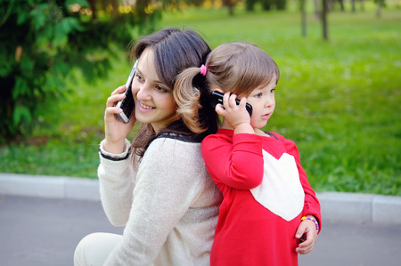 young parents: Mother and child talking on the phone