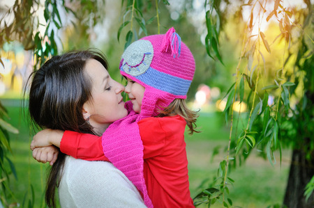 put together: daughter in a knitted cap with his mother in the park