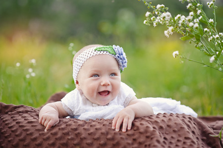 one little girl: baby smiling and looking up to camera outdoors in sunlight Stock Photo
