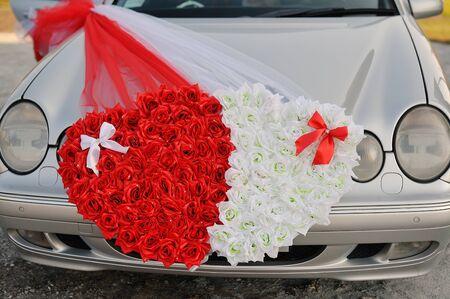 arreglo de flores: Coche de la boda adornado con dos corazones hechos de flores. Foto de archivo